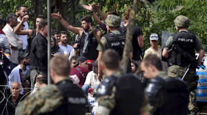Macedonian special policemen guard the border as more than a thousand immigrants wait at the border line of Macedonia and Greece to enter Macedonia near the Gevgelija railway station August 21, 2015. Macedonian police drove back crowds of migrants and refugees trying to enter from Greece on Friday after a night spent stranded in no-man's land by an emergency decree effectively sealing the Macedonian frontier. REUTERS/Ognen Teofilovski - RTX1P1K7
