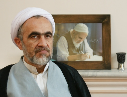 Ahmad Montazeri sits in front of a portrait picture of his late father Hossein Ali Montazeri